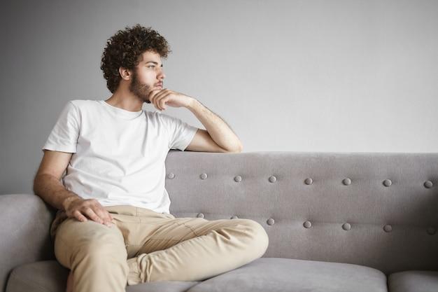 Concept de personnes et de style de vie. photo de beau jeune homme barbu sérieux ayant une expression faciale pensive, touchant son chaume, plongé dans ses pensées, réfléchissant, cherchant une solution au problème