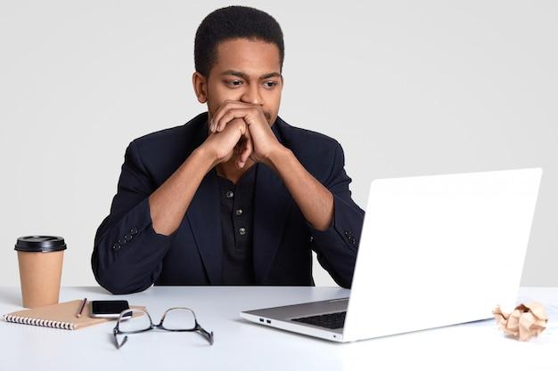 Concept de personnes, de technologie et de carrière. homme afro-américain aux cheveux bouclés, peau foncée, garde les mains près de la bouche, regarde attentivement les nouvelles commerciales sur internet, a des lunettes sur le bureau, isolé
