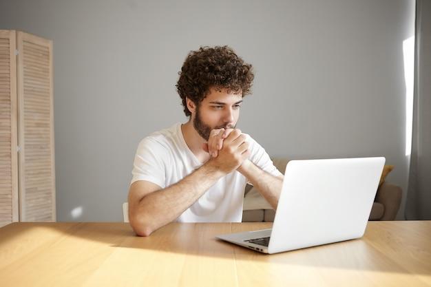 Concept de personnes, technologie moderne, communication, emploi et profession. élégant étudiant aux cheveux bouclés et barbe assis devant un ordinateur portable ouvert au bureau en bois, lisant un article scientifique en ligne