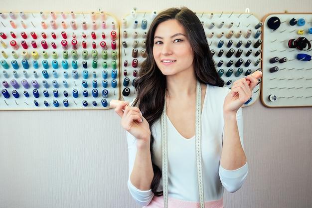 Concept de personnes, de travaux d'aiguille, de couture et de couture - femme sur mesure avec du fil en tissu de couture à l'aiguille. mains cousant avec une aiguille et du fil. doigts tirant le fil dans l'aiguille