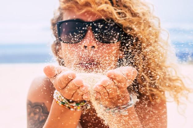 Concept de personnes en vacances d'été à la plage avec une belle jeune femme blonde défocalisée soufflant le sable de ses mains