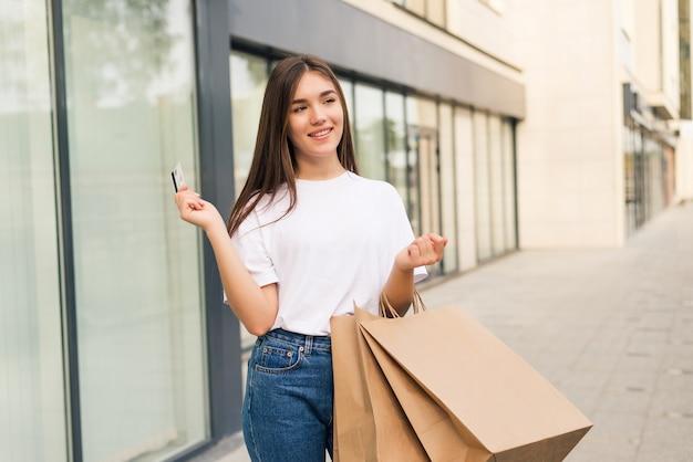 Concept de personnes, de vente et de consommation - gros plan d'une femme heureuse avec des sacs à provisions et une carte de crédit sur la rue de la ville