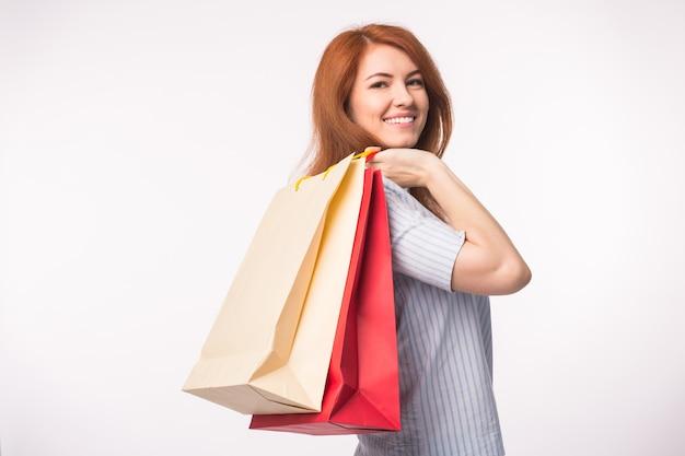 Concept de personnes, de vente et de consommation. jolie femme aux cheveux rouges sur blanc tenant des sacs à provisions.