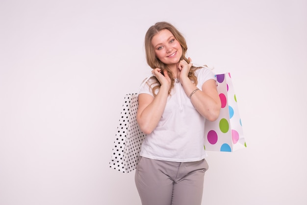 Concept de personnes, de vente et de consommation. jolie jeune femme blonde tenant des sacs multicolores sur fond blanc avec copie espace