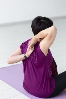 Concept de personnes, yoga, sport et soins de santé. close up of woman stretching hands up assis sur un tapis de yoga sur fond de salle blanche