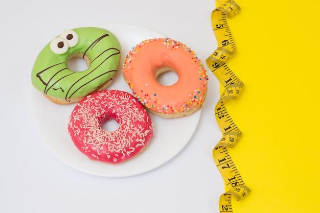 Concept de perte de poids. assiette pleine de beignets sucrés savoureux et ruban à mesurer. place pour le texte, vue de dessus