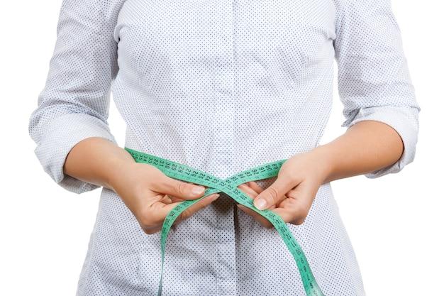 Concept de perte de poids et de mode de vie sain. femme de remise en forme mesurant son tour de taille avec un ruban à mesurer gros plan extrême