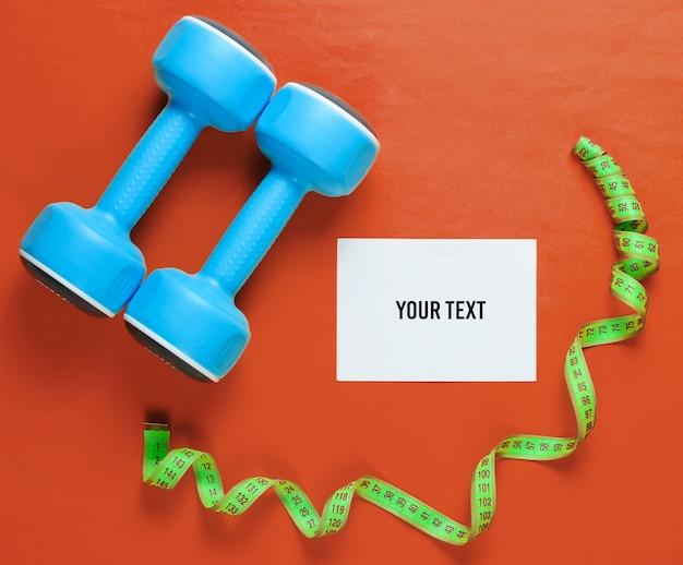 Concept de perte de poids de sport. haltères, règle, pilules sur fond orange. minimalisme. feuille de papier blanc pour l'espace de copie. vue de dessus