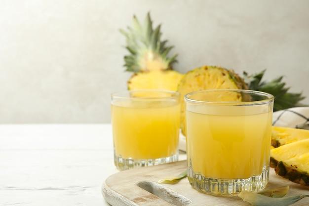 Concept de petit-déjeuner à l'ananas et verres de jus sur table en bois