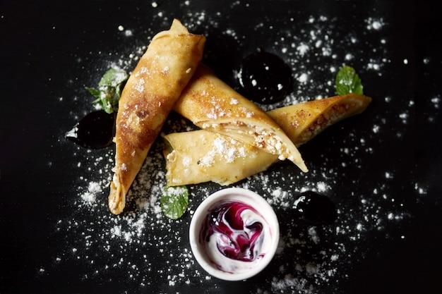 Concept de petit-déjeuner d'été sain savoureux. crêpes au fromage cottage à la menthe fraîche sur une plaque noire saupoudrée de sucre en poudre.