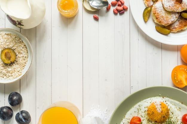 Concept de petit déjeuner. œufs sur le plat, pancakes au fromage blanc, prunes et flocons d'avoine avec lait, jus d'orange sur la table