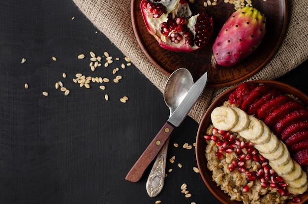 Concept de petit déjeuner de régime alimentaire sain. bouillie d'avoine à la banane, aux graines de grenade et au fruit de cactus opuntia. espace de copie. frais généraux, pose à plat