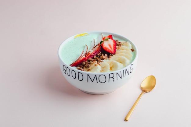 Concept de petit déjeuner sain. bol granola à grains entiers avec yogourt à la fraise, banane et menthe sur une plaque en céramique blanche gravée sur une surface rose. concept probiotique. vue de dessus avec copyspace