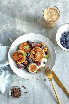 Concept de petit-déjeuner sain. crêpes au fromage avec myrtille, mûre, chocolat et feuilles de menthe