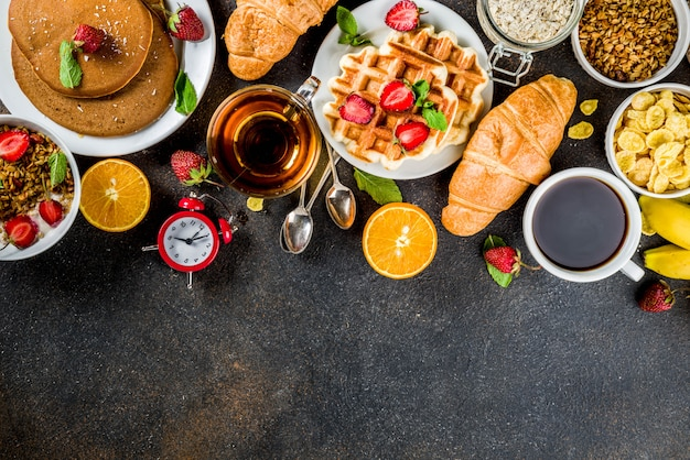 Concept de petit-déjeuner sain, divers plats du matin - crêpes, gaufres, sandwich à l'avoine et aux céréales avec yaourt, fruits, baies, café, thé, fond de jus d'orange