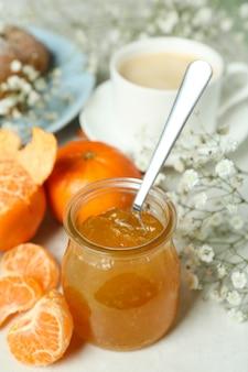 Concept de petit déjeuner savoureux avec de la confiture de mandarine sur une table texturée blanche