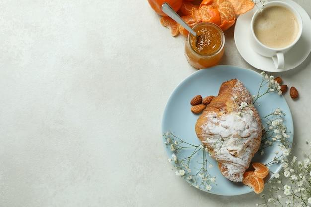 Concept de petit déjeuner savoureux avec croissant, confiture de mandarine et café sur une table texturée blanche