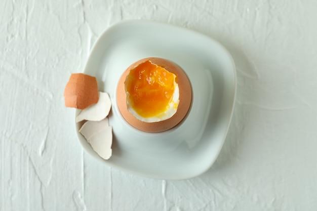 Concept de petit-déjeuner savoureux avec œuf à la coque sur table texturée blanche