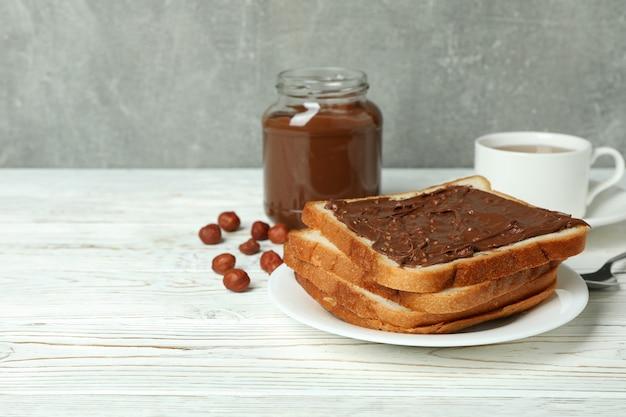Concept de petit déjeuner savoureux avec de la pâte de chocolat sur une table en bois blanche