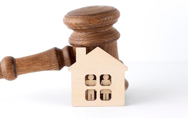 Concept de petite maison avec et marteau sur la surface en bois blanche