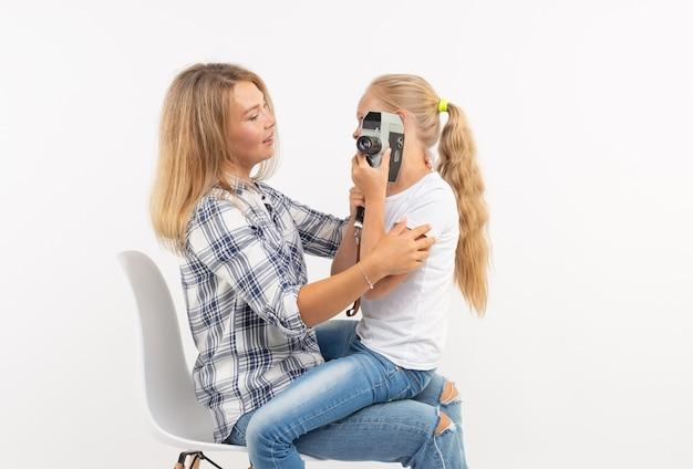 Concept photo, photographe et appareil photo rétro - jeune femme et sa fille adolescente utilisant un appareil photo vintage sur fond blanc.