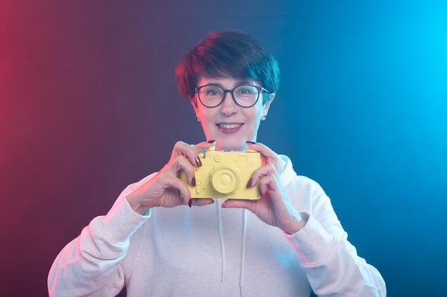 Concept de photographe, art et loisirs - femme de 50 ans tenir en main un appareil photo vintage jaune sur