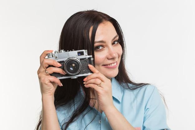 Concept de photographe, de passe-temps et de personnes - jeune femme brune avec appareil photo rétro sur fond blanc.