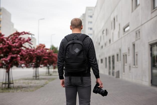 Concept de photographie et de créativité - vue arrière d'un photographe masculin avec un appareil photo reflex numérique moderne marchant dans la rue