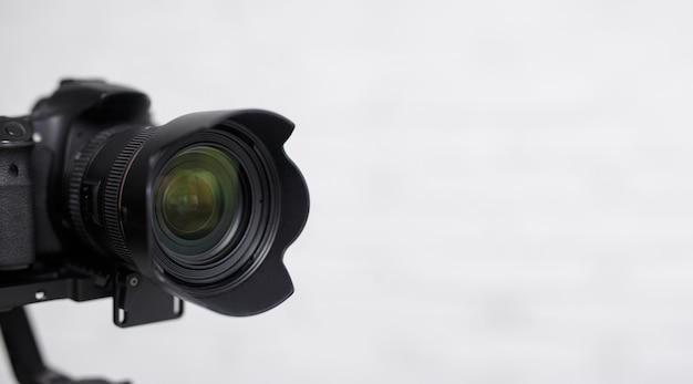 Concept de photographie et de vidéographie - gros plan d'un appareil photo reflex numérique moderne sur fond blanc avec espace de copie