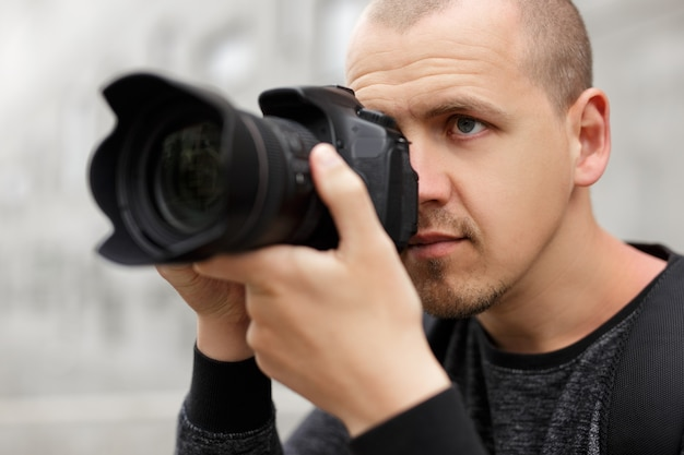 Concept de photographie, de voyage et de tourisme - portrait en gros plan d'un photographe masculin prenant une photo avec un appareil photo reflex numérique moderne