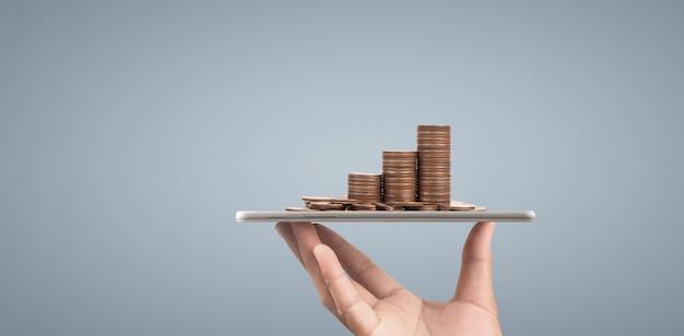 Concept de pièce de monnaie et de richesse. charges d'argent sur verre représentant tablette numérique