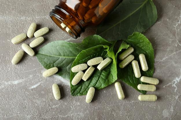 Concept de pilules de phytothérapie sur table texturée grise, vue du dessus