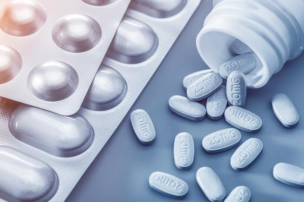 Le concept de pilules pour le traitement. pilules blanches en bouteille, sur table et sous blisters sur fond gris, isoler. copiez l'espace, tourné en studio.
