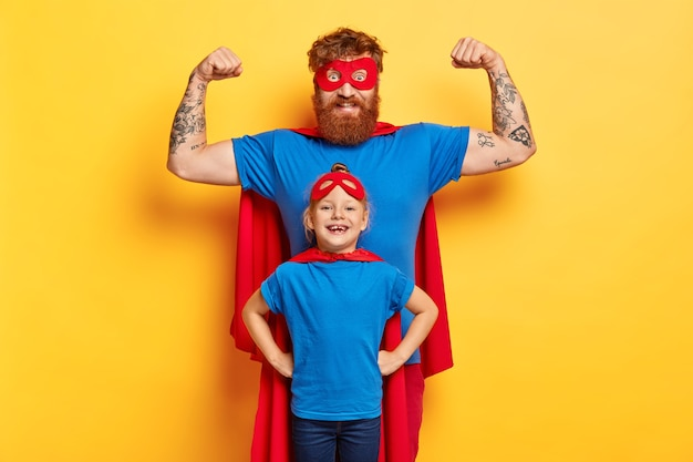 Concept de plaisir en famille. joyeux père fort lève les bras et montre des biceps, prêt à défendre sa fille