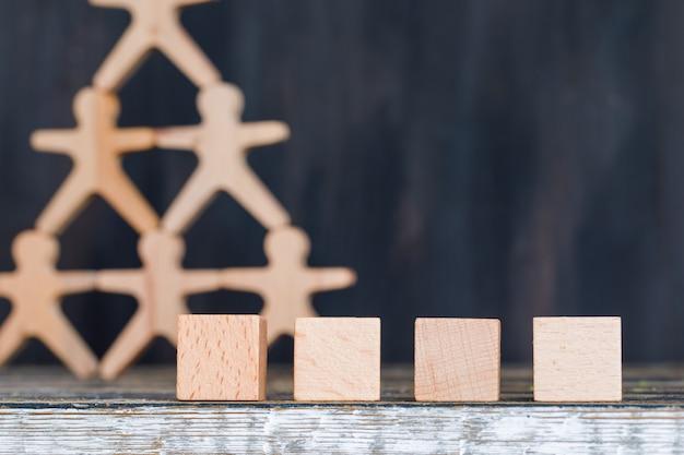 Concept de plan de marketing avec des figures en bois et des cubes sur la vue de côté de fond en bois et grunge.