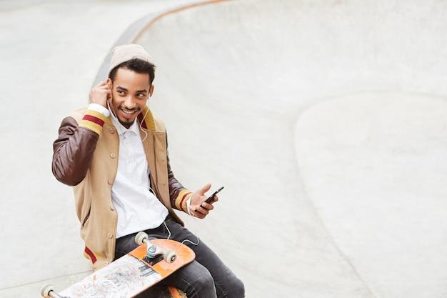 Concept de planche à roulettes. un adolescent élégant et insouciant fait du skateboard, se repose après une journée active,