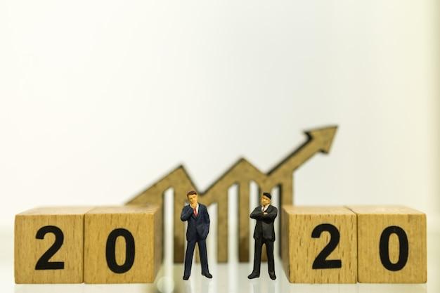 Concept de planification, d'affaires et d'objectifs 2020. grand plan, de, deux, homme affaires, figure miniature, gens, debout