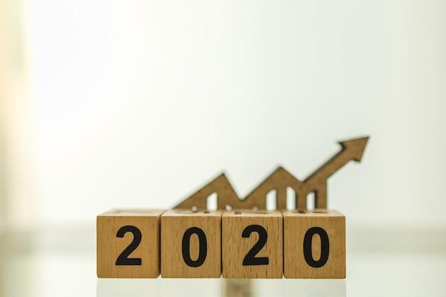 Concept de planification, d'affaires et d'objectifs 2020. gros plan des blocs de numéro en bois avec l'icône de flèche de graphique en bois difficile avec espace de copie.