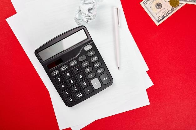 Concept de planification du budget, des affaires, de la planification financière, économiser de l'argent, des impôts ou du concept de comptabilité, de la faillite, de la vue de dessus ou de l'argent à plat, calculer, lister et stylo sur fond rouge