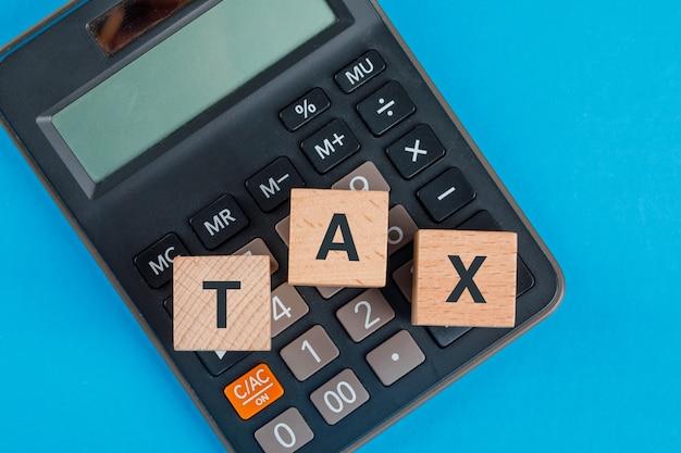 Concept de planification fiscale avec des cubes en bois sur la calculatrice sur table bleue à plat.