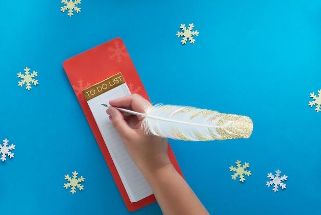 Concept de planification de noël, mise à plat avec main et planificateur de vacances sur papier bleu