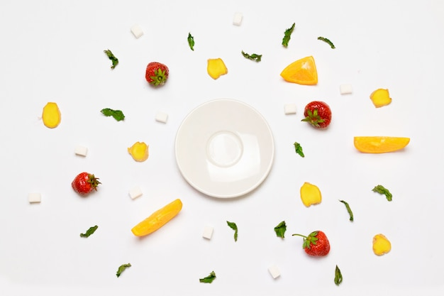 Concept de plaque blanche vide, morceaux de sucre, fraises, tranches de gingembre, feuilles d'orange et menthe