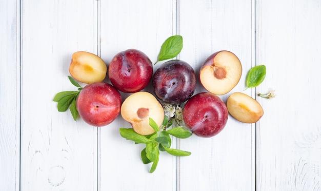 Concept à plat avec des prunes rouges juteuses et des feuilles vertes sur fond de bois blanc. image vue de dessus
