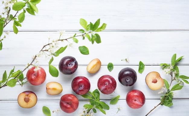 Concept à plat avec des prunes rouges juteuses et des fleurs de branche sur un fond de bois blanc. vue de dessus et copie de l'image de l'espace