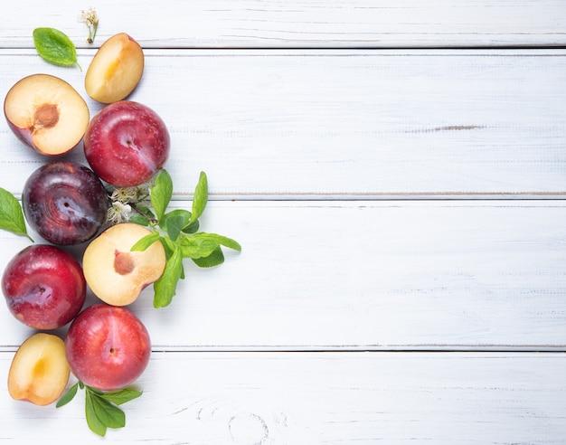 Concept à plat avec des prunes rouges juteuses et sucrées et des feuilles vertes sur fond de bois blanc. vue de dessus et copie de l'image de l'espace