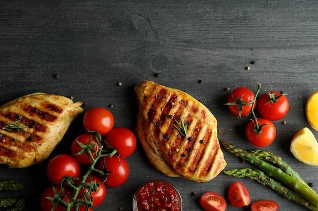 Concept de plats délicieux avec de la viande de poulet grillé sur fond de bois foncé