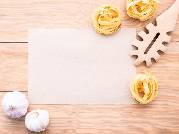 Concept de plats italiens et menu design papier vierge et louche de pâtes sur bois.