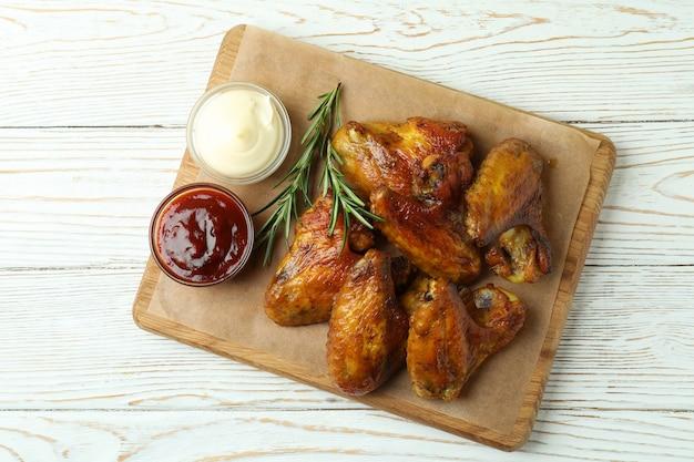 Concept de plats savoureux avec des ailes de poulet cuit au four sur fond en bois blanc