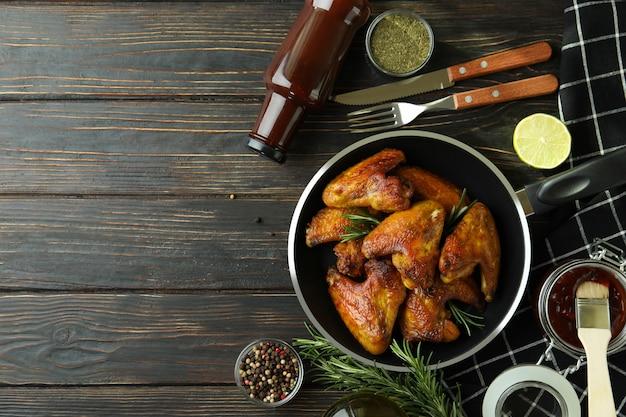 Concept de plats savoureux avec des ailes de poulet cuit au four sur fond de bois, espace pour le texte