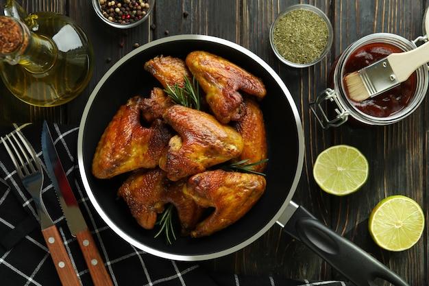Concept de plats savoureux avec des ailes de poulet cuit au four sur fond de bois